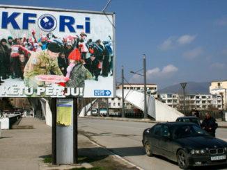 Kosovo  Un poliziotto fa un controllo di routine sul ponte di Mitrovica sul fiume Ibar, vicino a grande cartello del KFOR.