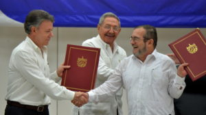 "Colombia's President Juan Manuel Santos (L) and Timoleon Jimenez, aka ""Timochenko"" (R), head of the FARC leftist guerrilla, shake hands accompanied by Cuban President Raul Castro (C) during the signing of the peace agreement in Havana on June 23, 2016. Colombia's govement and the FARC guerrilla force signed a definitive ceasefire Thursday, taking one of the last crucial steps toward ending Latin America's longest civil war. / AFP PHOTO / ADALBERTO ROQUE"