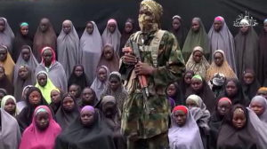 """This video grab image created on August 14, 2016 taken from a video released on youtube purportedly by Islamist group Boko Haram showing what is claimed to be one of the groups fighters at an undisclosed location standing in front of girls allegedly kidnapped from Chibok in April 2014. Boko Haram on August 14, 2016 released a video of the girls allegedly kidnapped from Chibok in April 2014, showing some who are still alive and claiming others died in air strikes. The video is the latest release from embattled Boko Haram leader Abubakar Shekau, who earlier this month denied claims that he had been replaced as the leader of the jihadist group. / AFP PHOTO / HO / RESTRICTED TO EDITORIAL USE - MANDATORY CREDIT """"AFP PHOTO / BOKO HARAM"""" - NO MARKETING NO ADVERTISING CAMPAIGNS - DISTRIBUTED AS A SERVICE TO CLIENTS"""