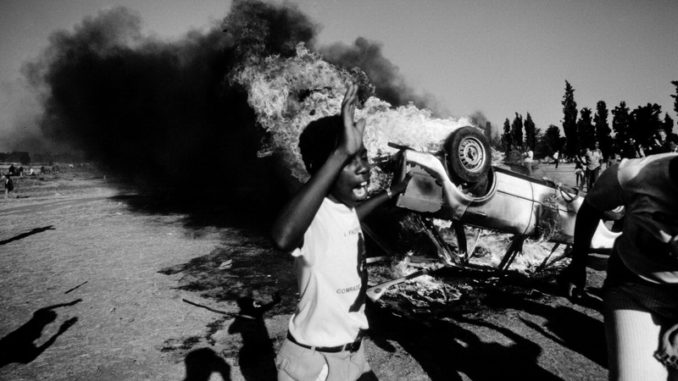 As a car bus behind him, a young South African participates in a civil disturbance outside the Auduza Cemetery.