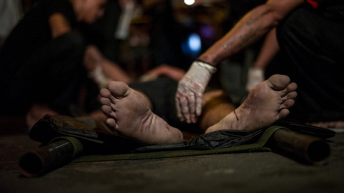 """In this picture taken on September 24, 2016, medics check the dead body of an alleged drug dealer gunned down by unidentified men in Manila. Philippine President Rodrigo Duterte defended his threat to kill criminals as """"perfect"""" and vowed no let-up in his war on crime, as the death toll surged past 3,700. / AFP PHOTO / NOEL CELIS"""
